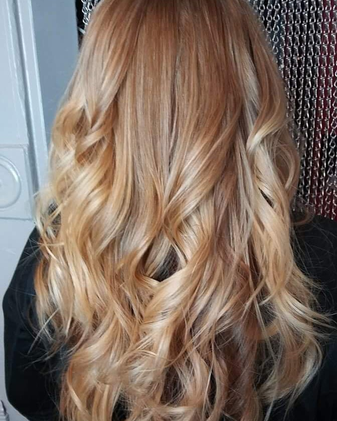 warm blonde color with curly hairstyle